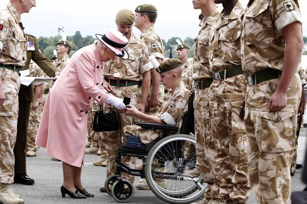 Queen Elizabeth II presents a campaign medal to Shaun Stocker during the Drumhead Service of Thanksgiving to mark the return of the 1st Battalion Royal Welsh Chester Racecourse